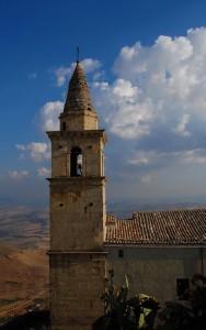 Campanile in maiolica e paesaggio estivo siciliano