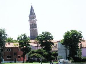 Chiesa con torre pendente di Burano che si eleva tra il verde del giardino.