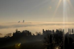 Campanile nella nebbia con raggio di sole