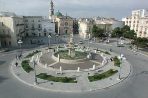Fontana monumentale con sfondo Chiesa della Maddalena