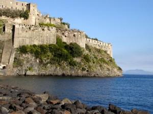 Le mura del Castello Aragonese e Procida sullo sfondo