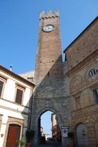 torre merlata con orologio e porta