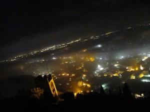 da Marostica le luci di Nove si fanno spazio nella nebbia