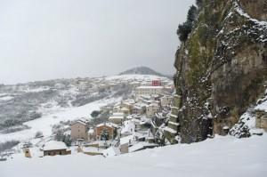 """Sotto la neve con la """"roccia"""" che domina sulle case"""