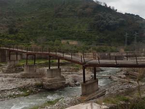 Vecchio ponte in disuso sulla fiumara con passerella di fortuna