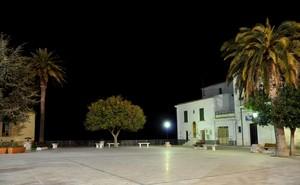 Piazza Vittorio Veneto di sera con un albero affacciato alla ringhiera sul mare