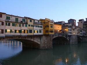 Le luci della sera si accendono sull'Arno