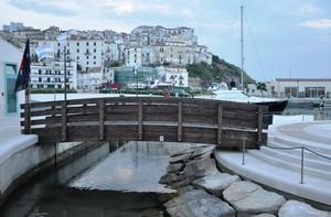 Ponte di legno nel porto con l'antica Rodi G. alle sue spalle