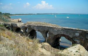 ruderi di ponte romano sulla spiaggia