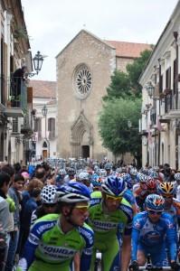 Ciclisti in corsa con la Chiesa di S. Francesco a Lucera (FG)