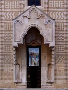 Protiro e portale tra i disegni geometrici in carparo e pietra calcarea